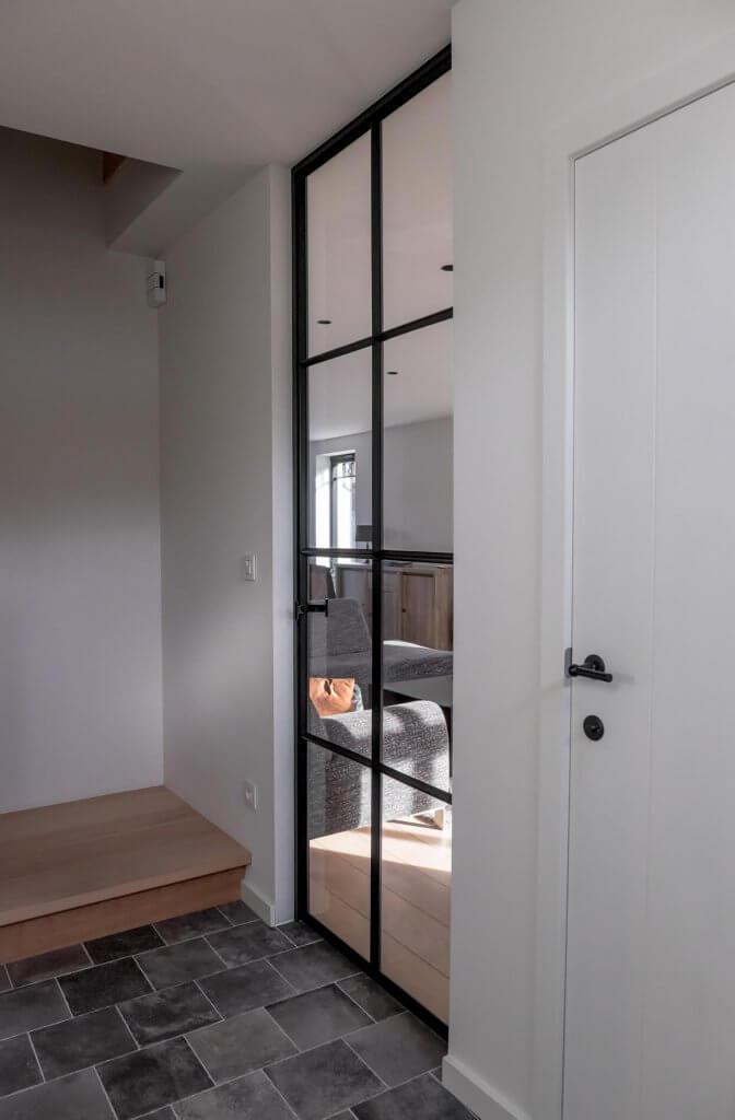 Stalen deur met glas, ruiten zijn afgewerkt met zwarte stopverf
